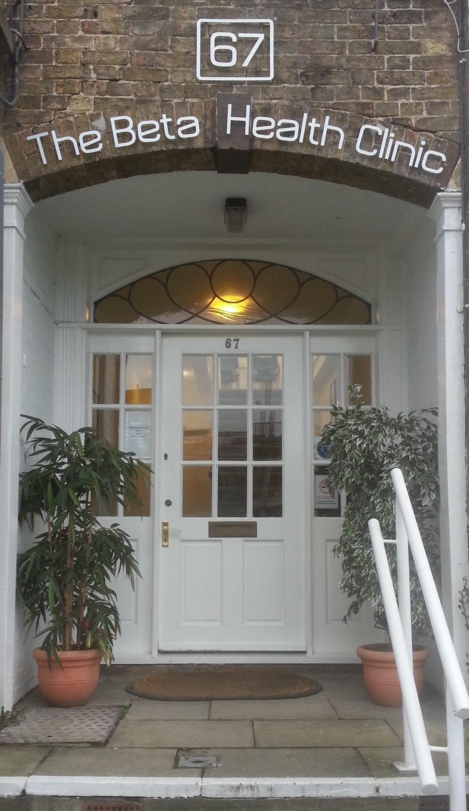 The entrance to our building with stone porch and white front door flanked by plants in tubs