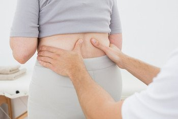 A therapist massaging a patient's lower back