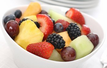 A white bowl of fresh melon, berries and grapes