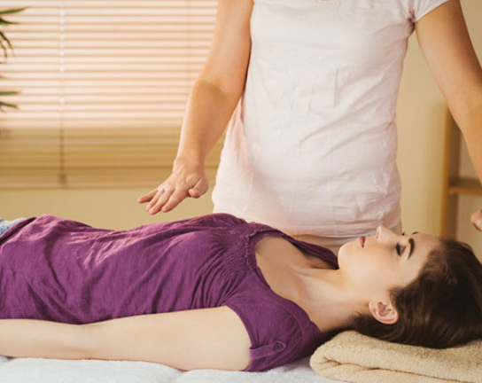 A therapist's hands hovering above a patient in a Reiki session