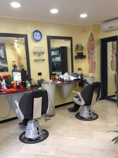due sedie davanti a degli specchi all'interno di un parrucchiere