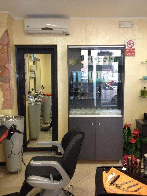 interno di un parrucchiere con vista di una sedia, uno specchio e un mobile con dei cosmetici