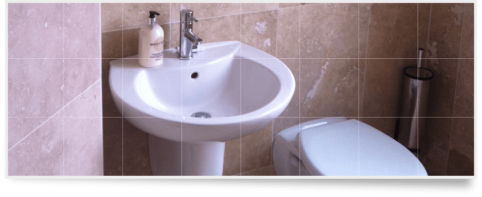 Bathroom with marble wall tiles and ceramic sink and toilet