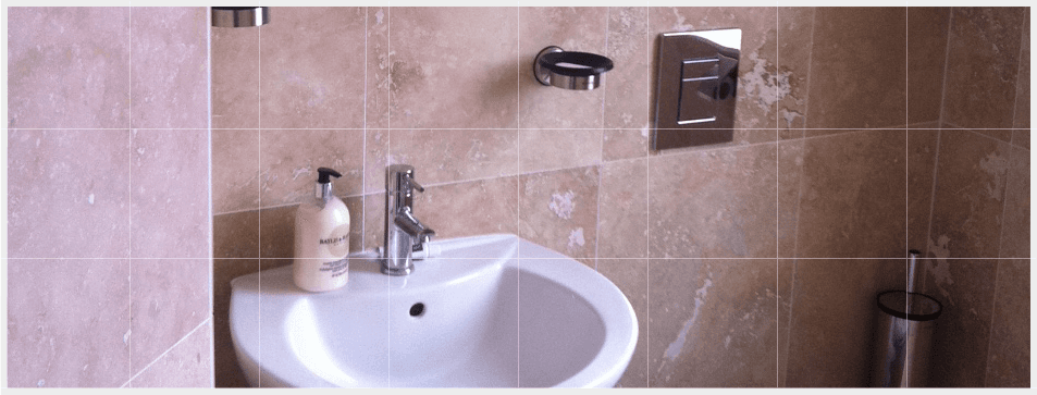 Bathroom with marble wall tiles and ceramic sink