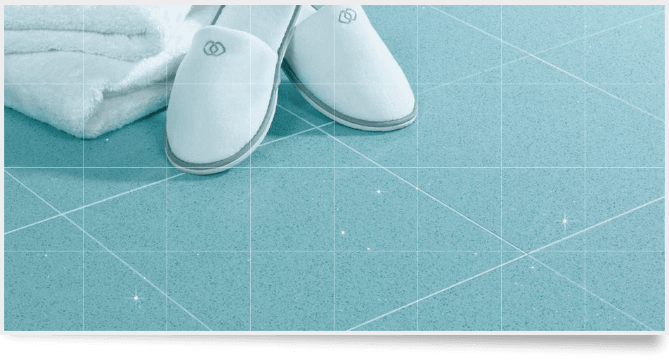 White towel and slippers on a blue bathroom floor tiles with sparkly metallic specks