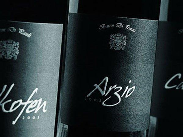 tre bottiglie di vino nere con delle etichette con scritto Arzio