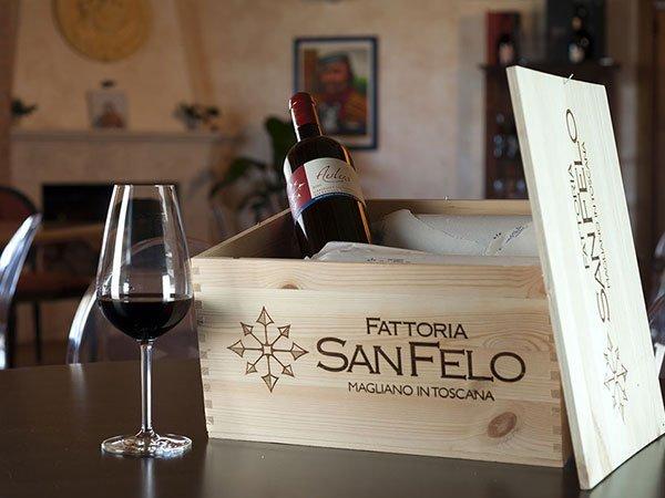 una bottiglia di vino dentro a una cassa di legno e un bicchiere con del vino rosso su un tavolo