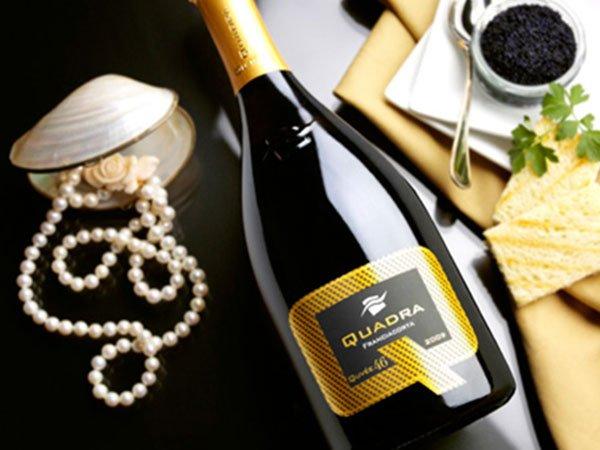 Bottiglia di spumante marca Quadra e accanto una collana di perle dentro a una conchiglia