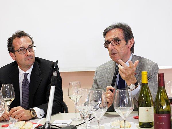 due persone eleganti sedute a tavola con dei bicchieri e bottiglie di vino