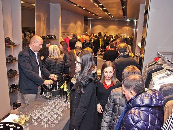 delle persone in piedi durante un evento di degustazione di vini in un negozio di vestiti