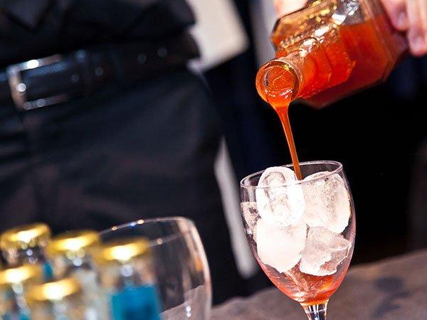un bicchiere con dentro del ghiaccio e sopra una bottiglia che versa del liquore arancione