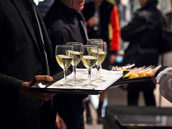 un uomo con in mano un vassoio con sopra dei bicchieri di vino bianco