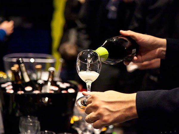una mano che versa dello champagne in un bicchiere