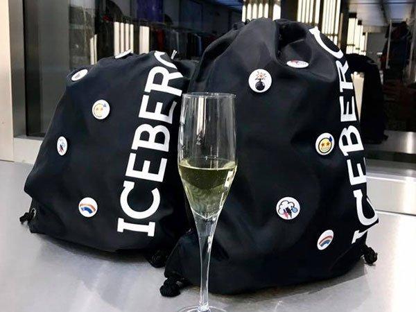 degli zaini neri con scritto Iceberg e un bicchiere di vino bianco