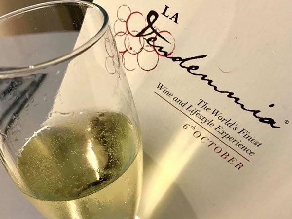 un bicchiere di vino e accanto un menù bianco con scritto La Vendemmia