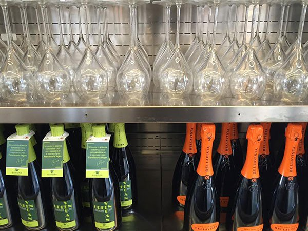 delle bottiglie di spumante arancioni e verdi e sopra dei bicchieri su una mensola d'acciaio