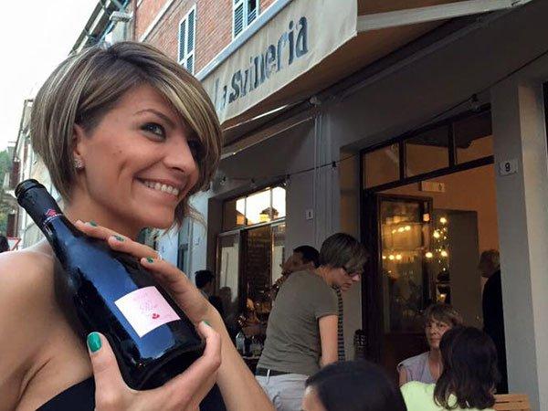 una donna con capelli corti con delle meches vista di lato mentre sorride con in mano una bottiglia nera di vino