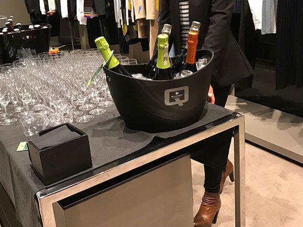 un secchio nero con dentro delle bottiglie di spumante e accanto una serie di bicchieri e vista delle gambe di d una donna con stivali marroni