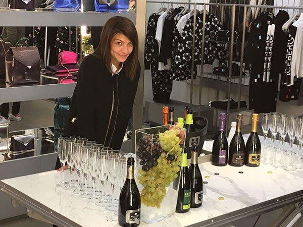 una ragazza in piedi appoggiata a un tavolo mentre sorride con davanti una serie di bicchieri e delle bottiglie di spumante