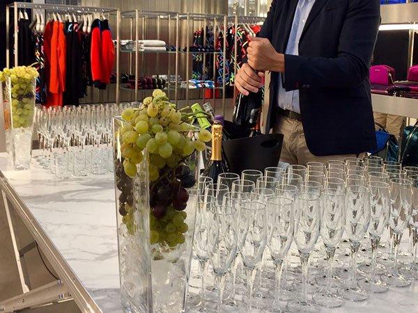 un uomo che sta stappando una bottiglia di spumante, accanto dei bicchieri  e dell uva dentro a dei grandi bicchieri di vetro