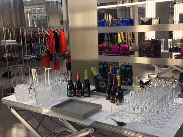 un tavolo con sopra delle bottiglie e dei bicchieri in un negozio di vestiti