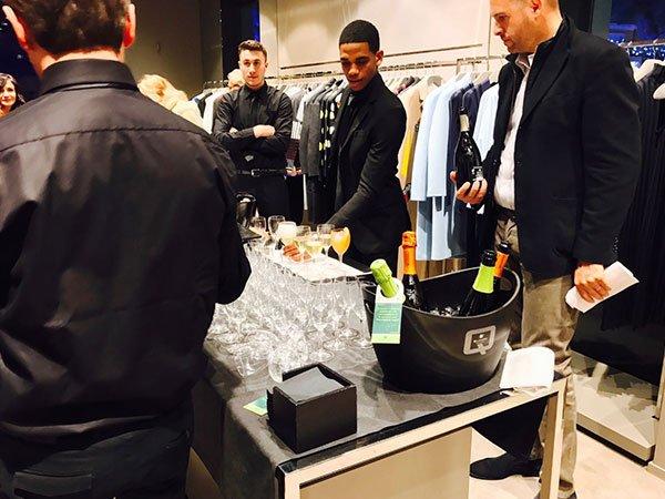 degli uomini in piedi vicino a un tavolo con dei bicchieri e bottiglie di spumante dentro a un secchio nero
