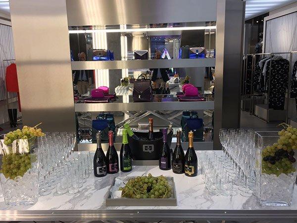 delle bottiglie di spumante, dei bicchieri e dell'uva, il tutto su un tavolo all'interno di un negozio di vestiti