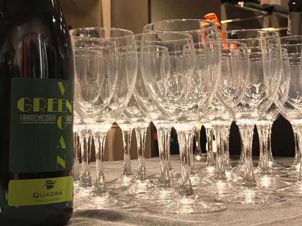 una bottiglia di vino e accanto dei bicchieri