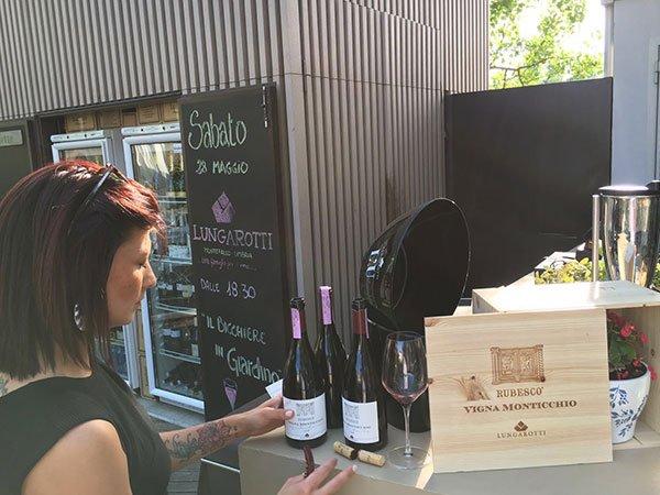 una donna in piedi di fianco a una cassa di spumante,  tre bottiglie e un bicchiere di vino rosso