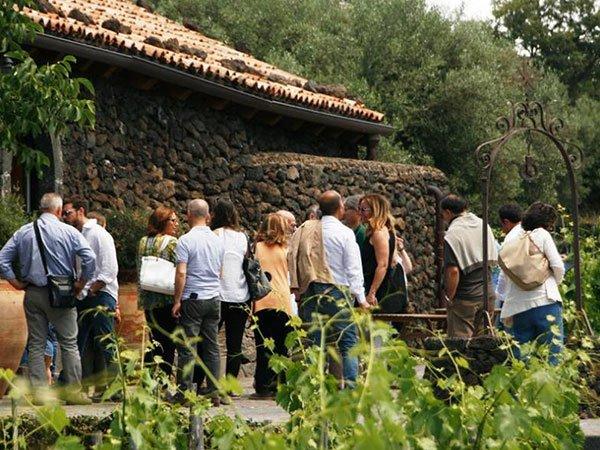 delle persone in piedi vicino a una casa in pietra