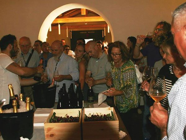 delle persone in piedi vicino a un tavolo con  delle casse di uva, bottiglie di vino e un secchio di ghiaccio con dentro delle bottiglie di spumante