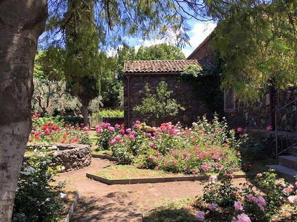 un giardino con fiori rosa, alberi aiuole di pietra e una casa in pietra