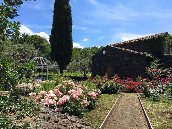 un giardino con fiori rosa, rossi e viola, un gazebo in ferro bianco, un cipresso e una casa in pietra