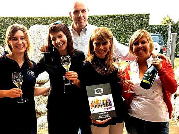 quattro donne sorridenti con dei bicchieri in mano e dietro un uomo