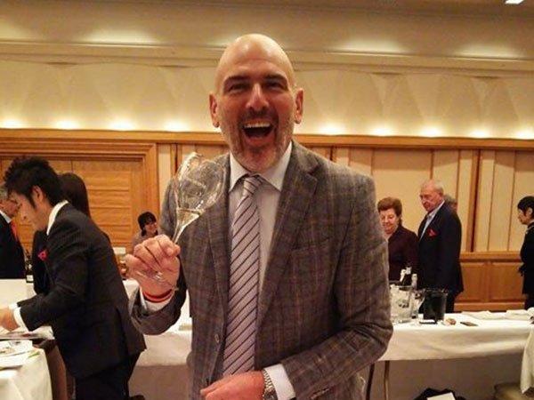 un uomo sorridente con un bicchiere di vino in mano