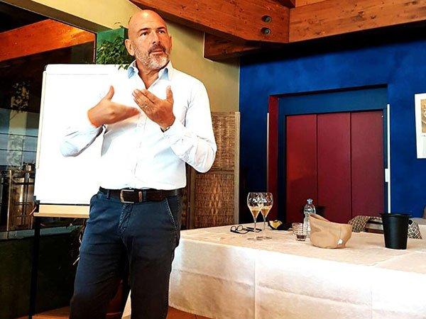 un uomo in piedi che gesticola, dietro una lavagna a fogli e un tavolo con due bicchieri di vino e altri oggetti accanto