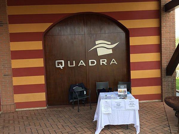 una porta di legno con scritto Quadra e davanti un tavolo con una tovaglia bianca e tre piccole sedie nere