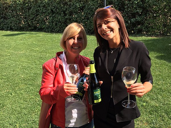 due donne in piedi in un prato di un giardino sorridenti con in mano dei bicchieri e delle bottiglie di vino
