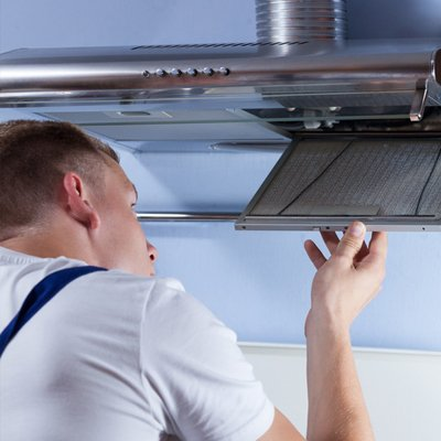 technician looking at kitchen exhaust interior