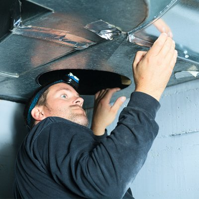 worker inspecting air duct quality
