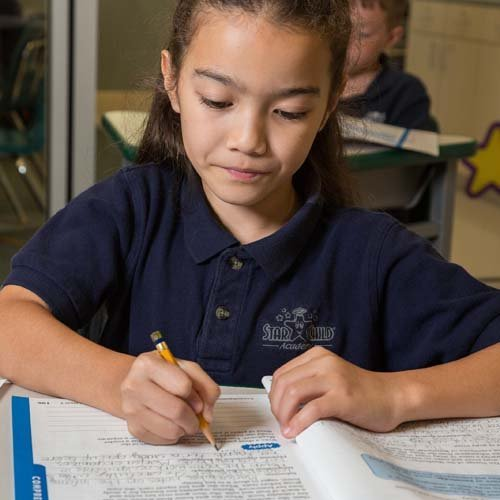 Girl Sitting at Desk in StarChild Academy's Private Elementary School