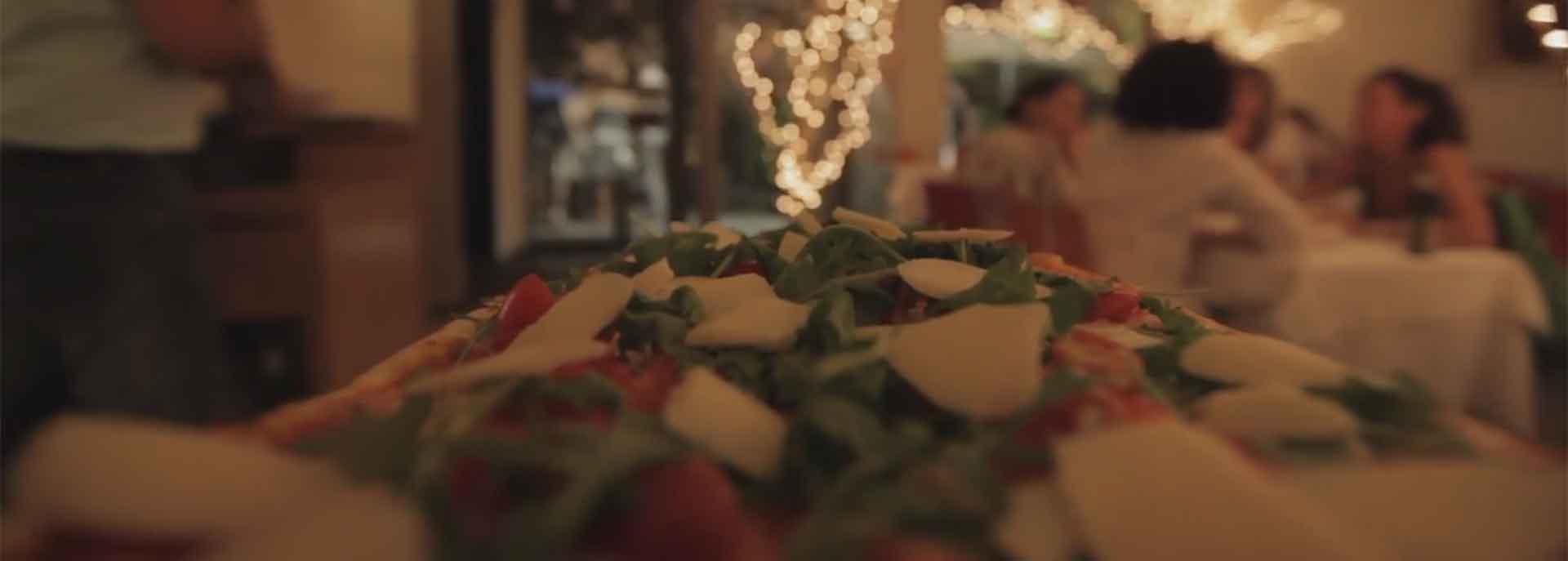 primo piano di una pizza farcita con un tavolo di donne sullo sfondo