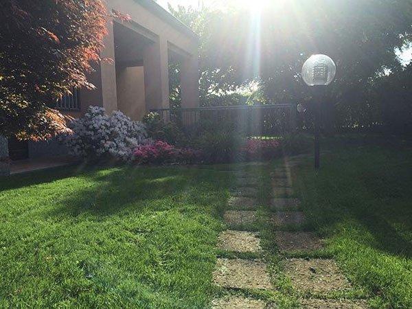 Un prato verde davanti una villa , un'aiuola con piante fiorite, una camminata e un lampione nel giardino