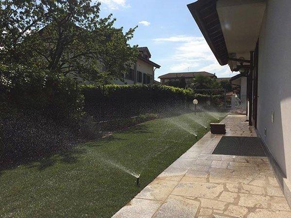 Un prato con un impianto di irrigazione e sulla destra un villa