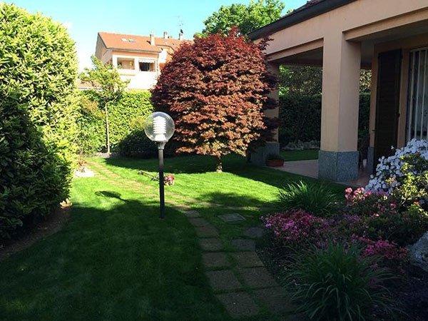 Una villa e sul lato destro un prato con caminatta e sulla destra un aiuola con piante fiorite