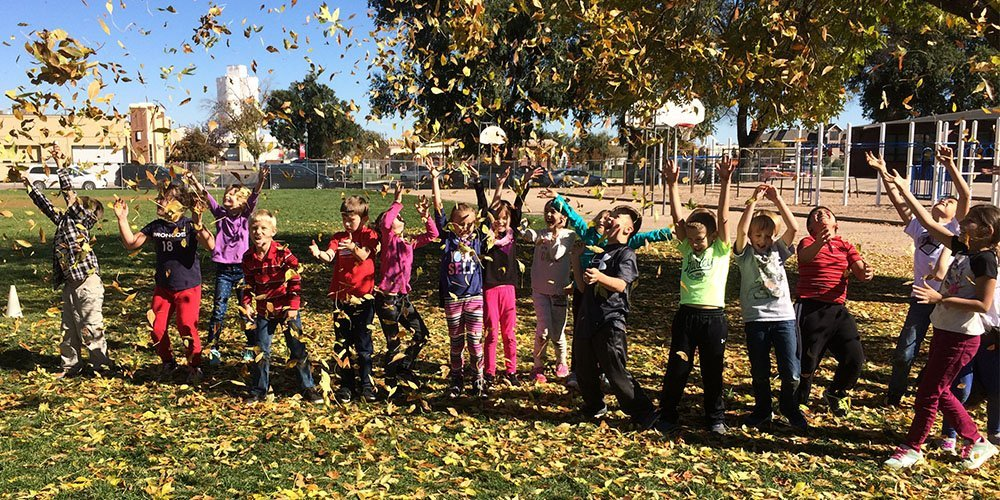 Students playing in the leaves on the playground