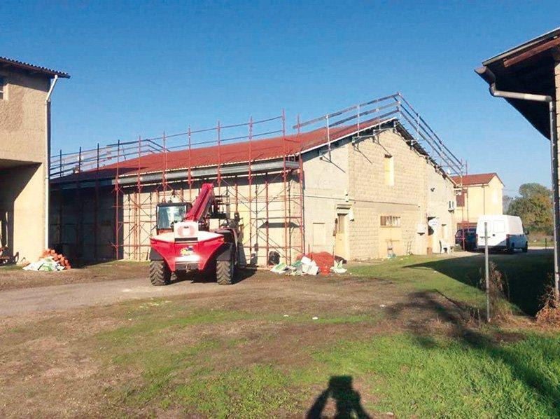 una casa con un'impalcatura rossa e un mezzo da lavoro