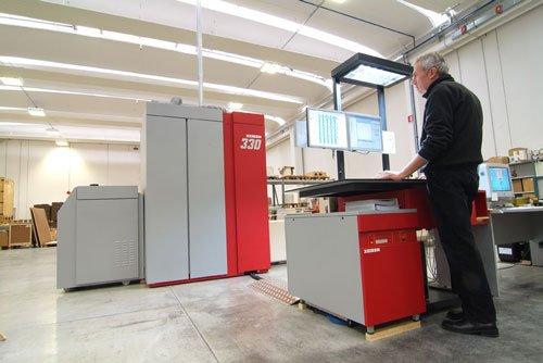un uomo al lavoro con davanti dei monitor in una fabbrica