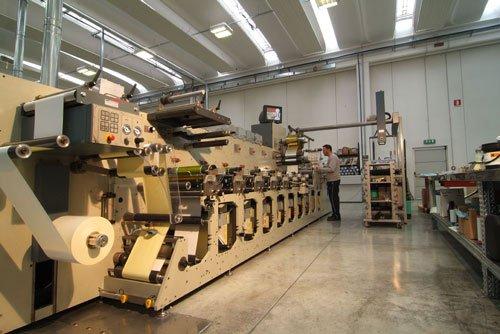 un macchinario per le etichette e un uomo al lavoro