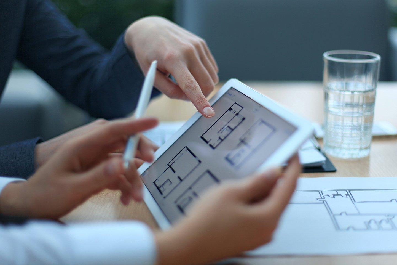 agente immobiliare che mostra i piani di casa su tavoletta elettronica